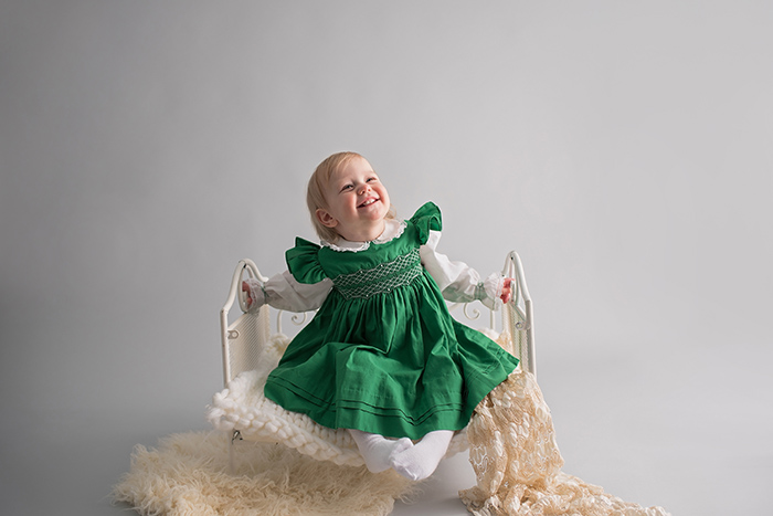 a baby sits in a white iron bed wearing an old fashioned green smocked dress smiling