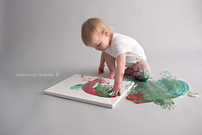 a girl uses her hand to paint a canvas during her one year milestone smash session in ottawa photography studio