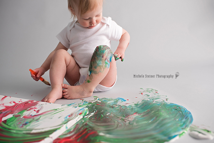 a girl paints her leg with her hand during her milestone smash photography session in ottawa studio