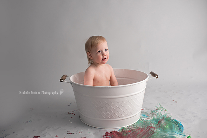 a girl sits in a white metal tub filled with water and bubbles for her one year milestone paint smash in ottawa photography studio