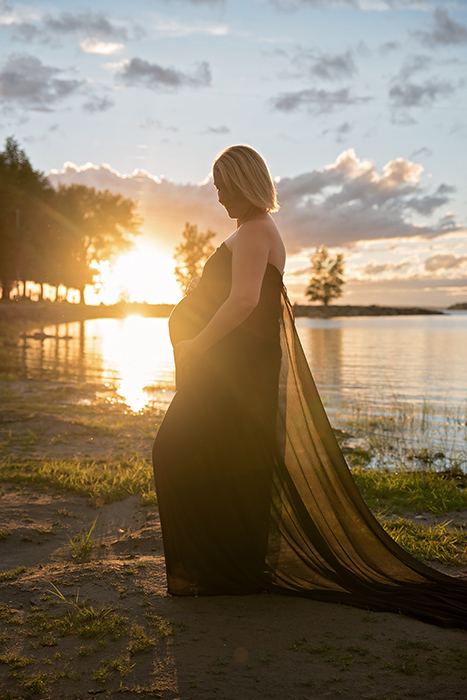 a mother stands at brittania beach in ottawa with the setting sun glowing near her pregnant belly