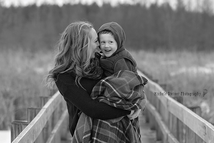 a mother holds her son resting her face on his giving him affection and love outside in winter in ottawa