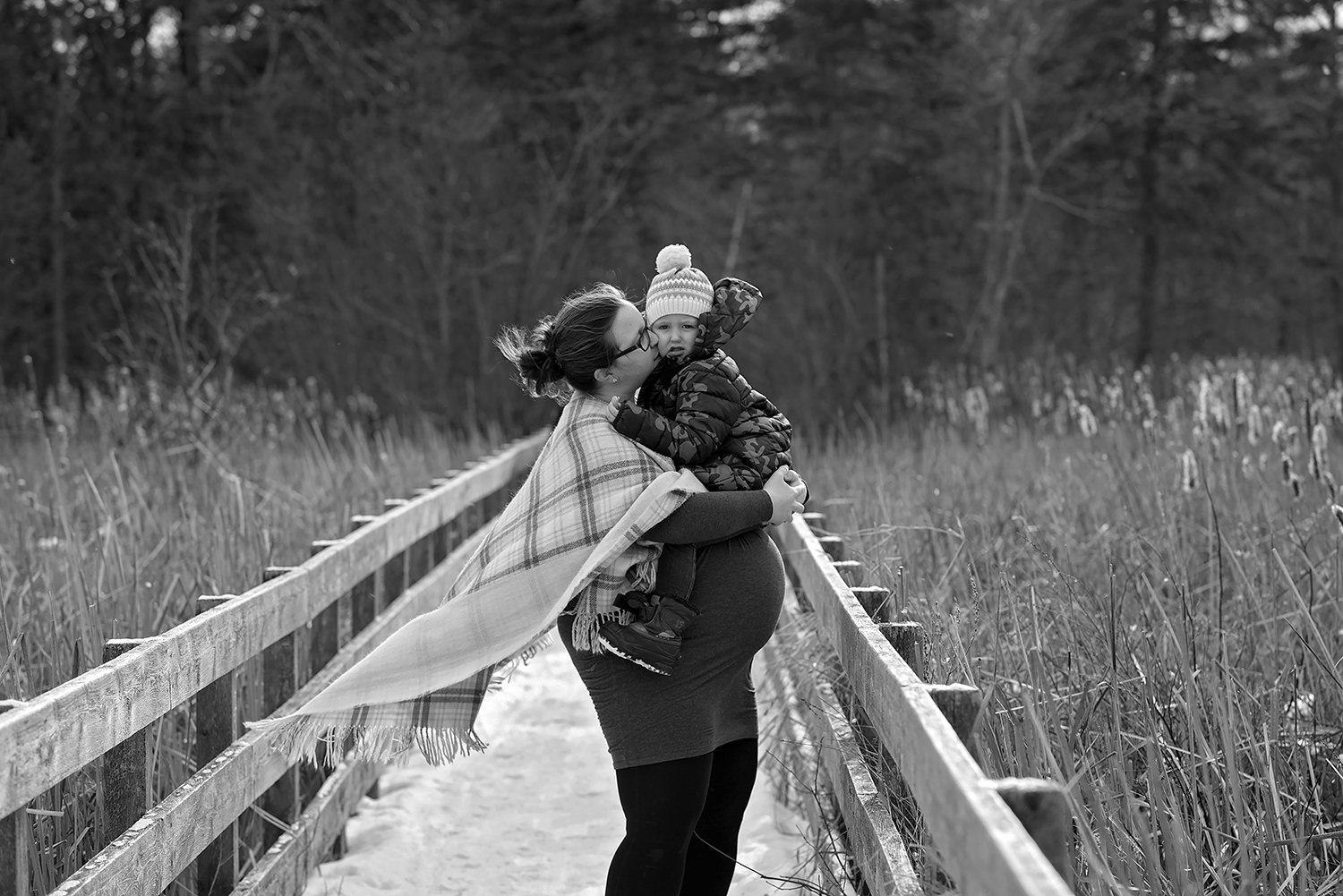 a pregnant mother holds her toddler daughter in her arms kissing her on the cheek outside in winter