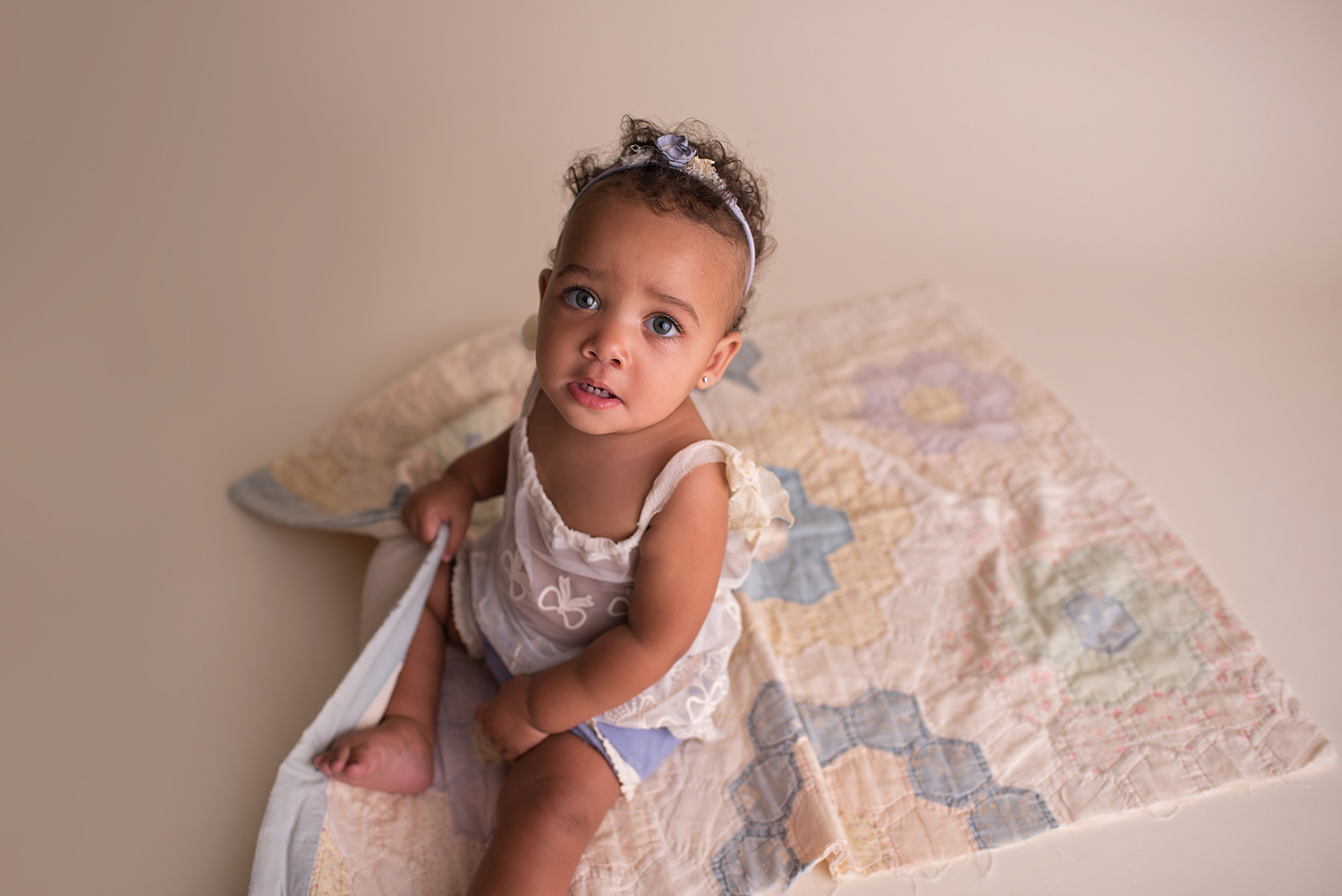 a six month old baby sits on a quilt looking up at camera wearing a lace upcycled outfit
