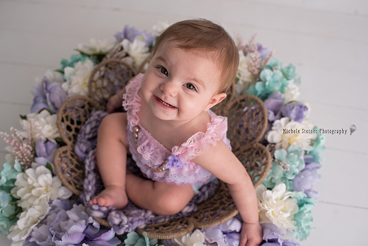 a little girl sits in a twine basket with flowers all around her smiling up at the camera