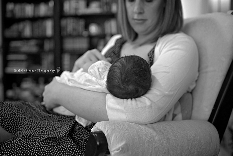 a mother sits in a rocker nursing her baby back of head seen