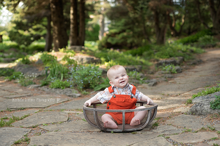 a infant boy sits in a wood bowl outside in a garden with a happy squinty expression on his face