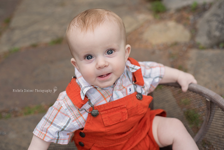 a baby boy sits in a wood bowl on a stone path looking up at the camera with two little teeth showing