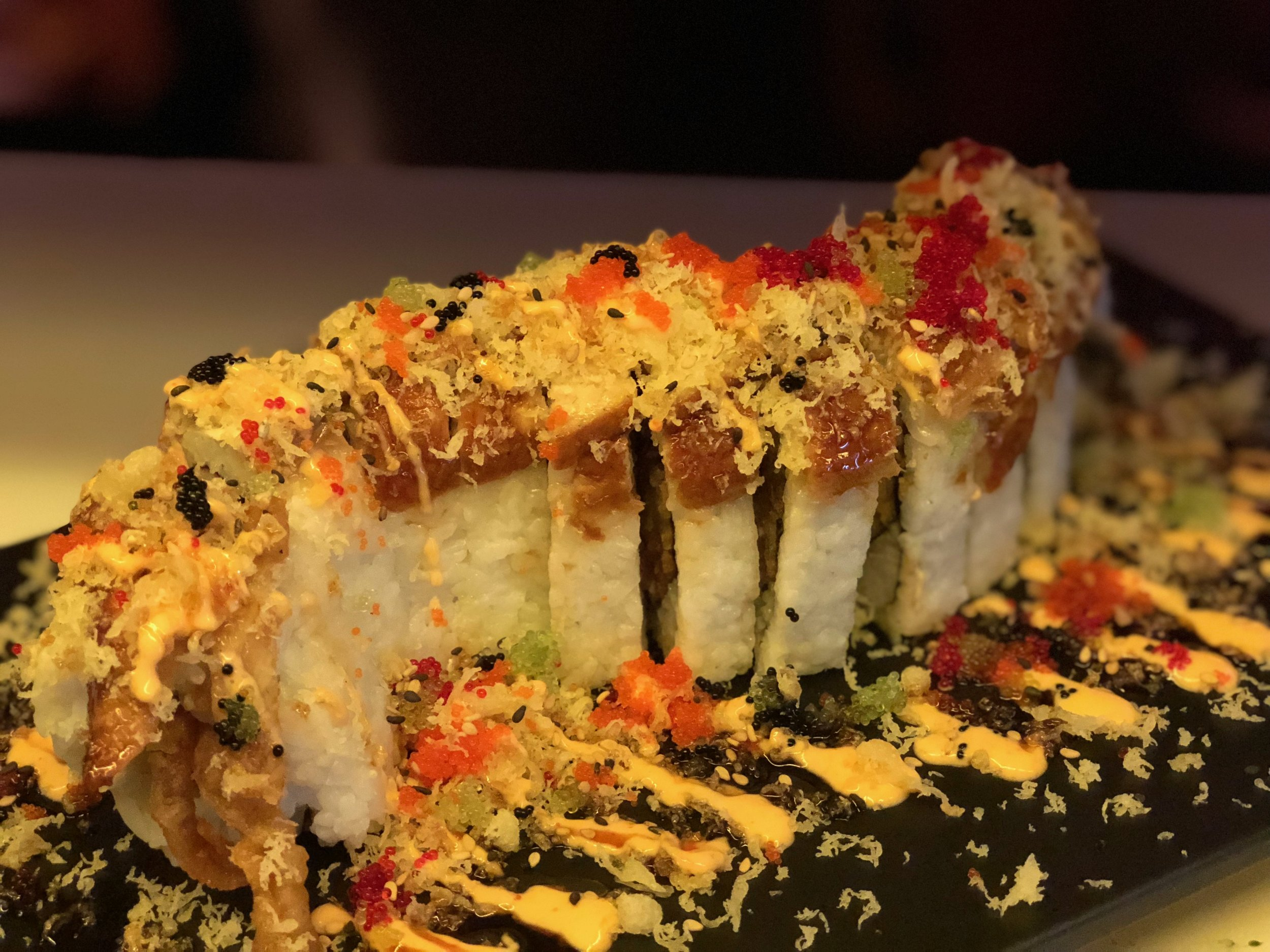 Monster Roll - Soft Shell Crab, Asparagus, Avocado, Krab, Cream Cheese topped with Eel, Tempura flake, colorful fish egg, Spicy Mayo and Eel Sauce.