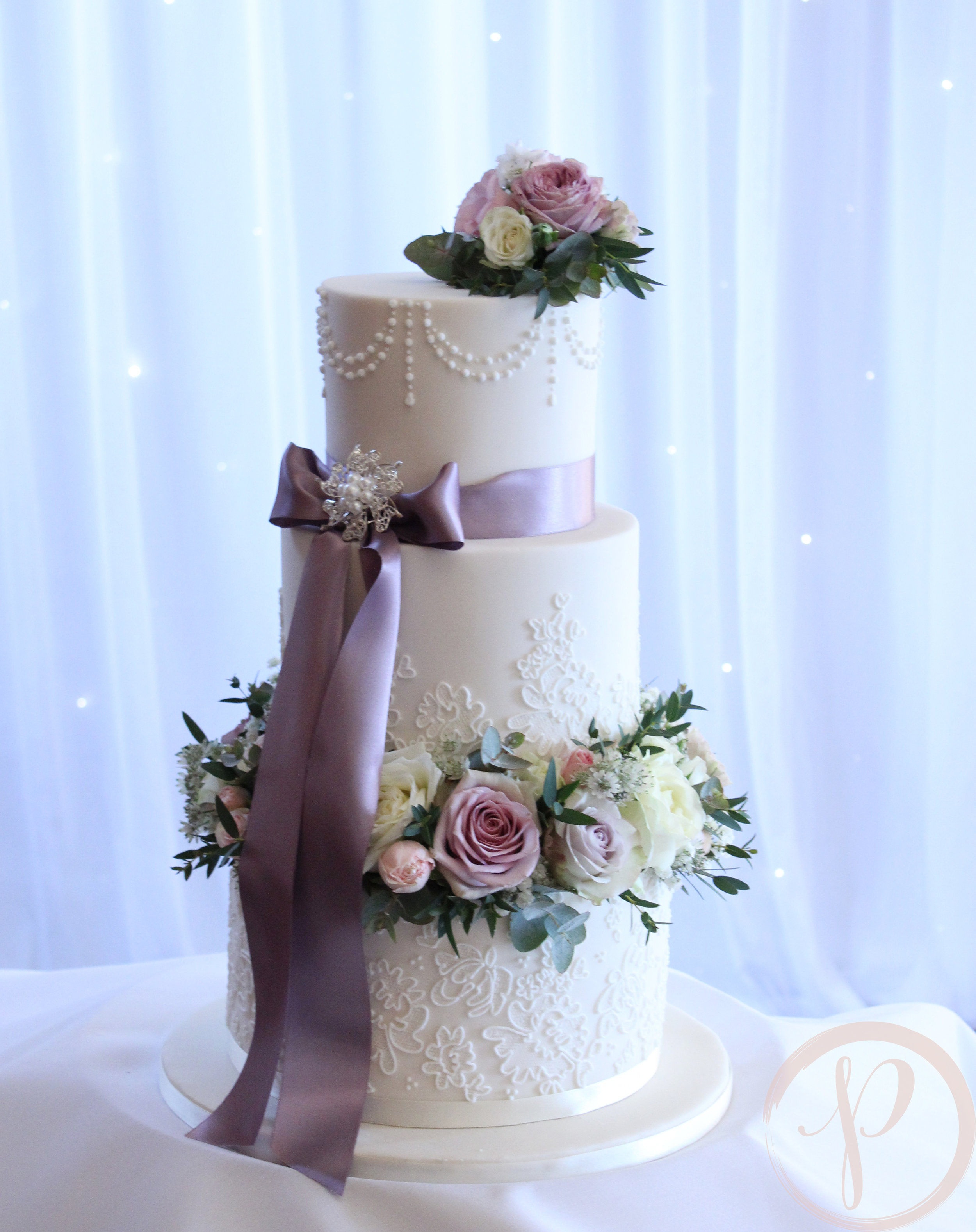 fresh flower and lace wedding cake with bow.jpg