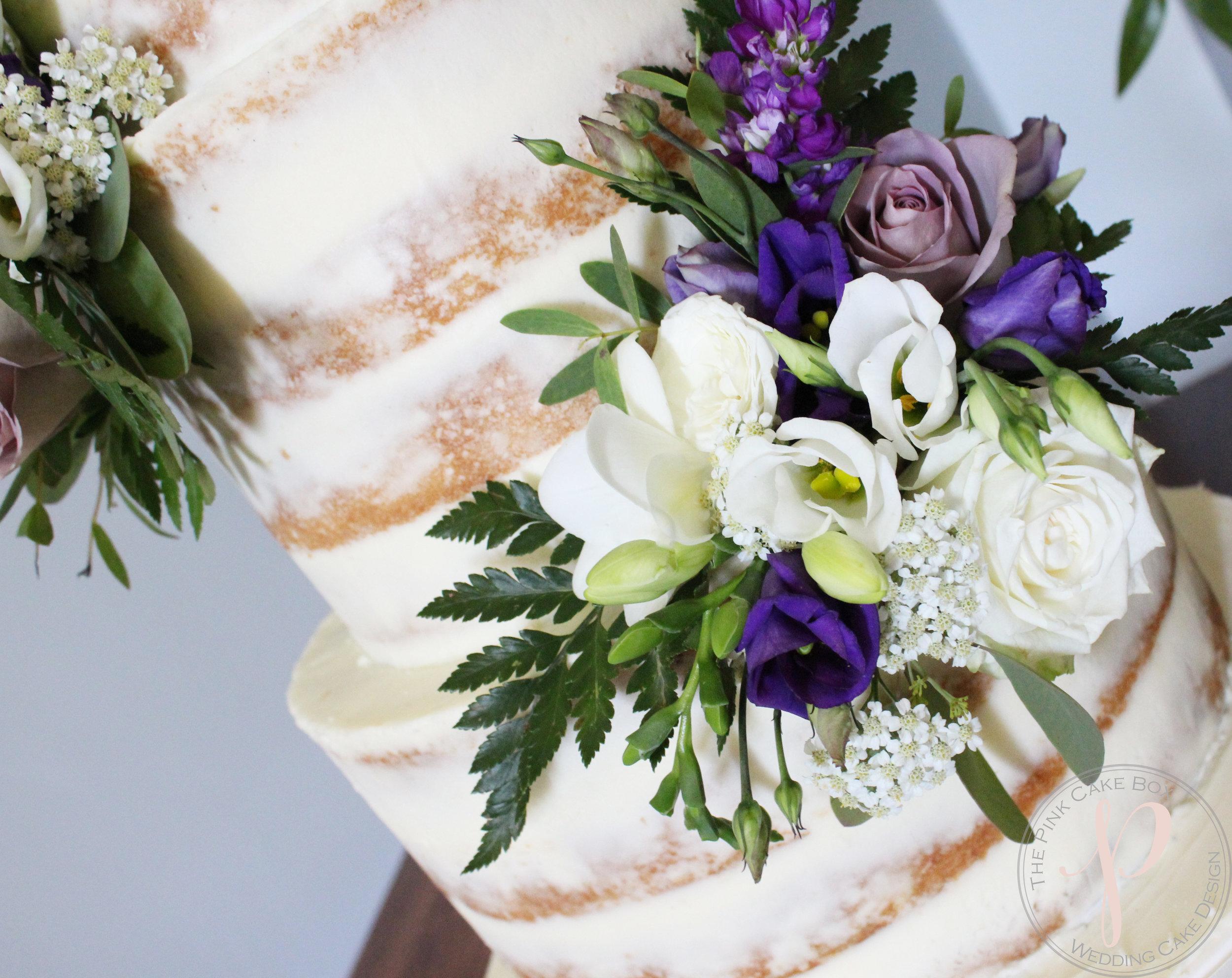 semi naked wedding cake purple and ivory fresh flowers.jpg