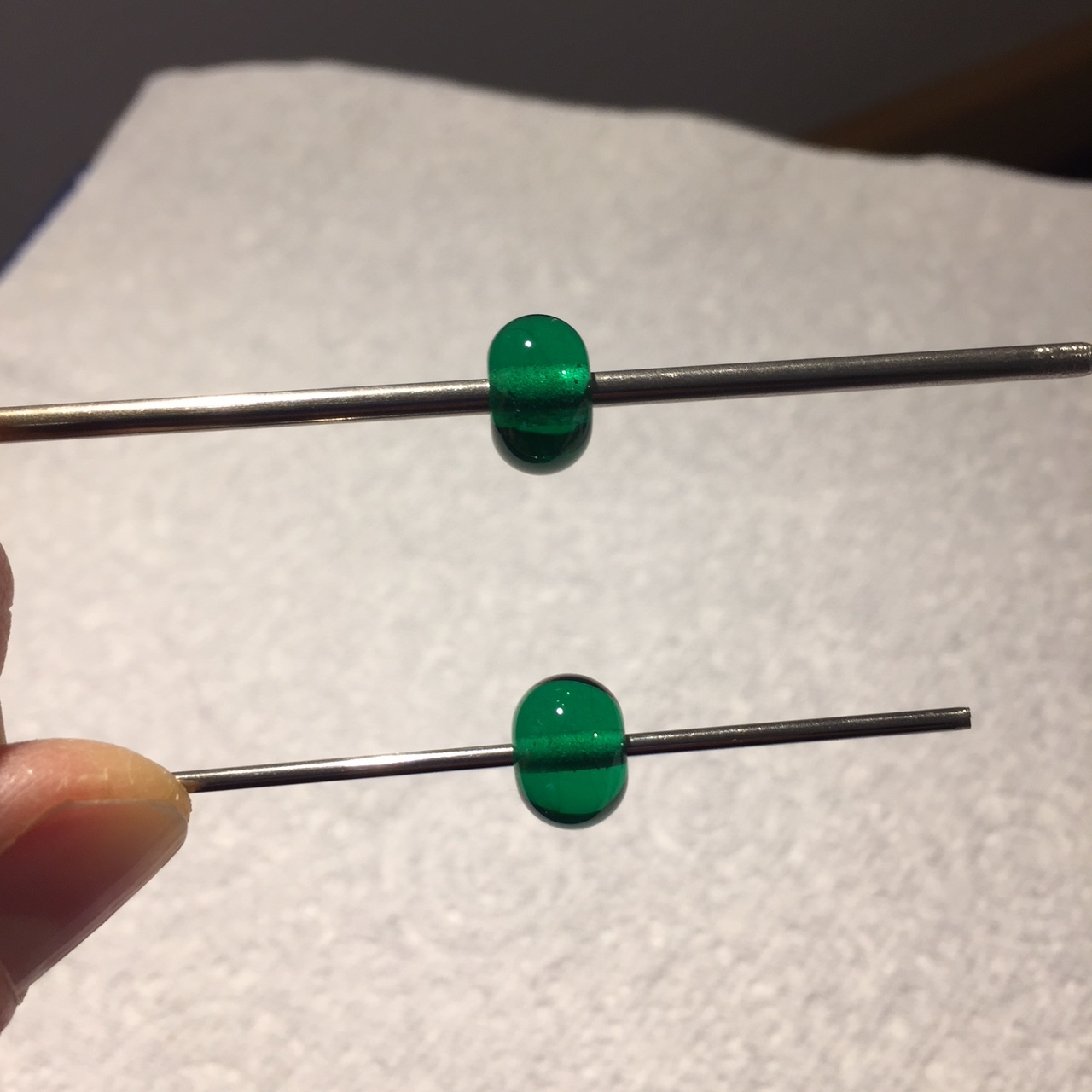 In this image the bead holes have been filed clean of bead release - this already makes them more attractive. Notice the difference in the shapes of the beads. Top - 2.4mm; bottom - 1.6mm.