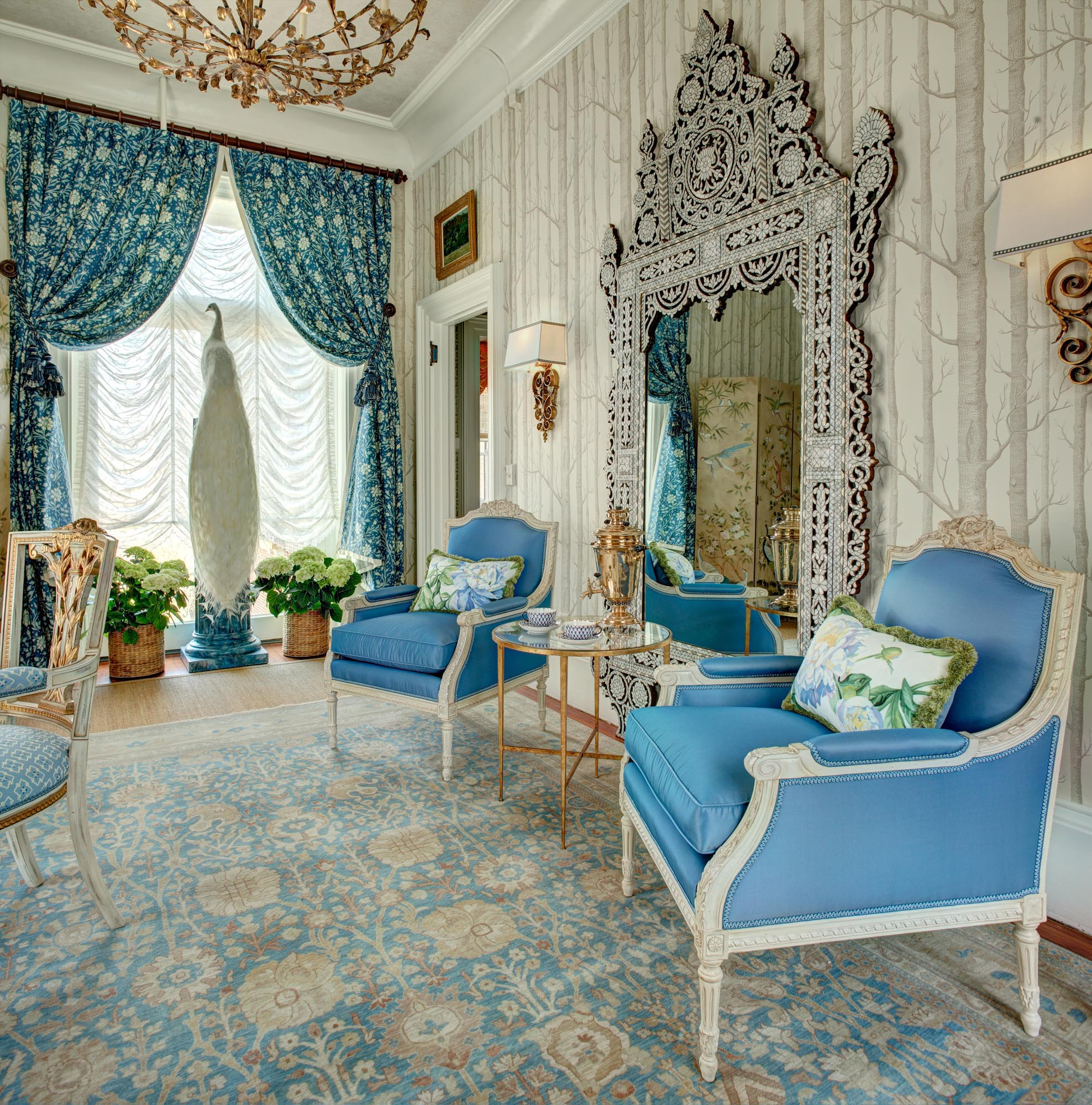 Living room with blue chairs and mirror in the wall
