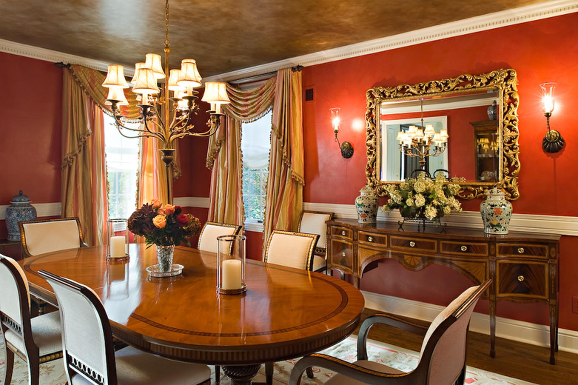 Warm dining area in red paint with table for six and vintage chandelier