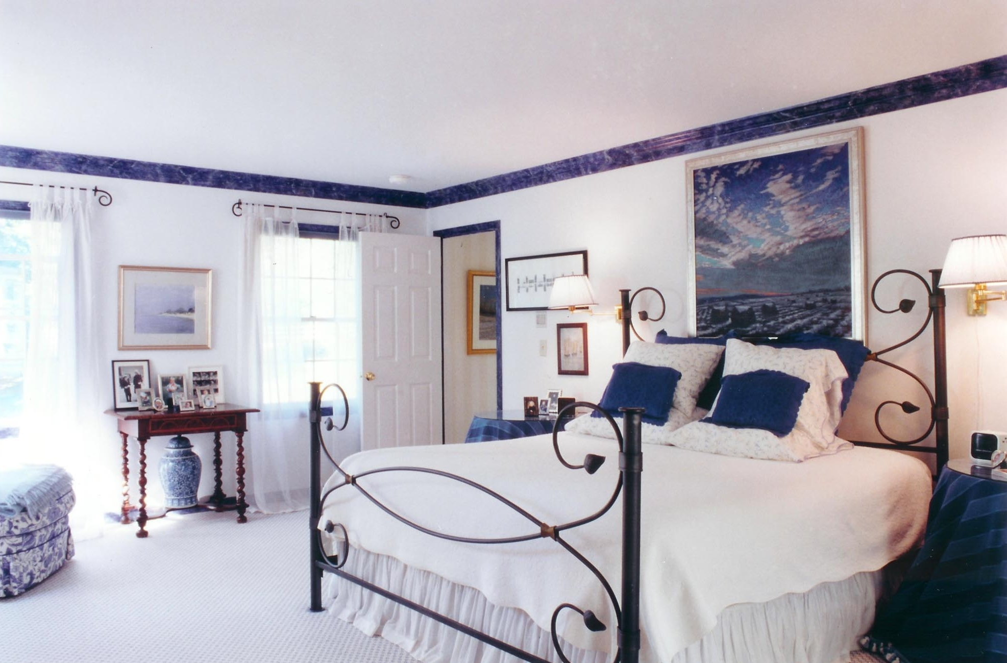 Bright bedroom with white beddings and paintings on the wall