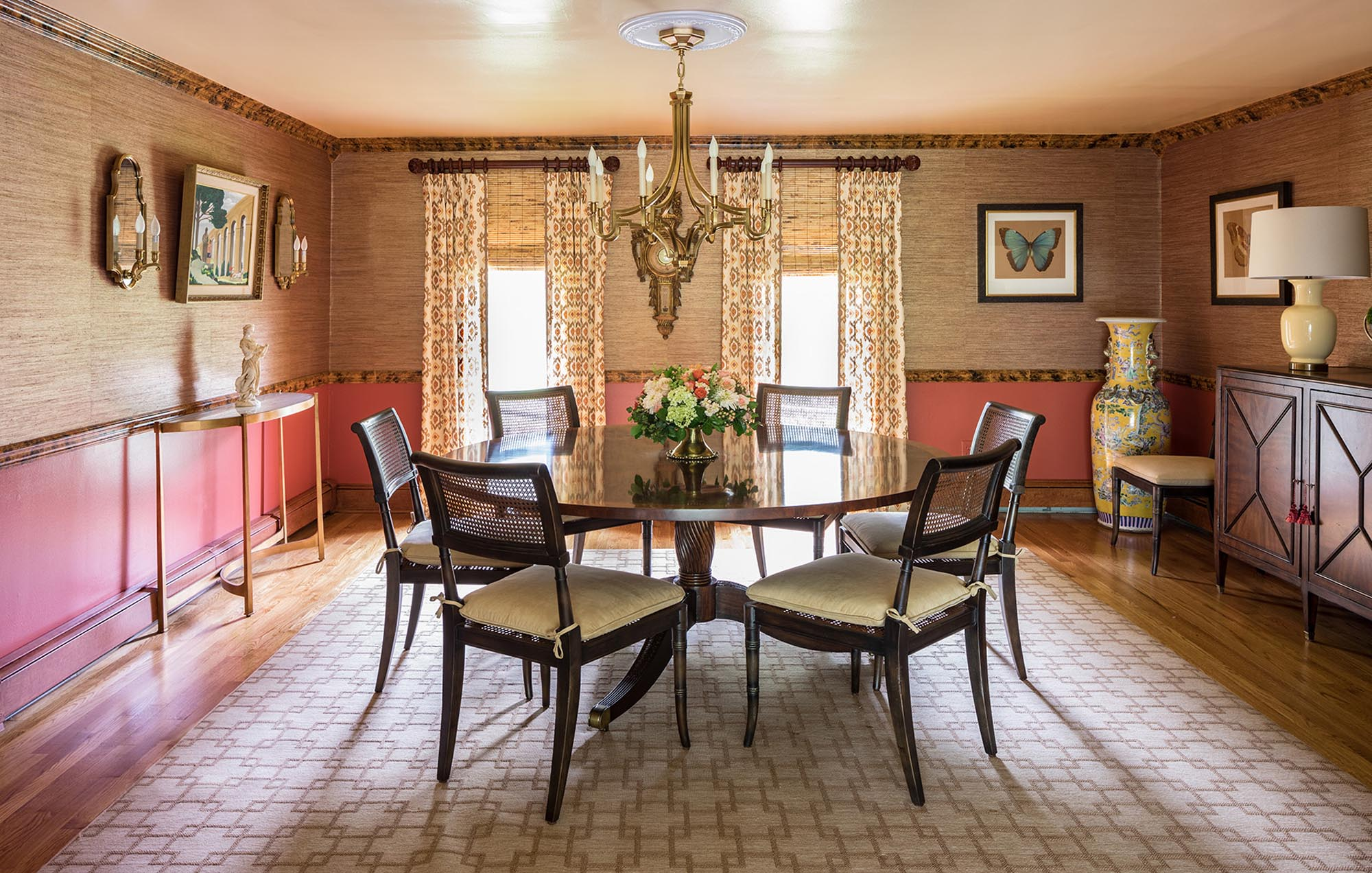 Warm dining area with round dining table for six and printed carpet