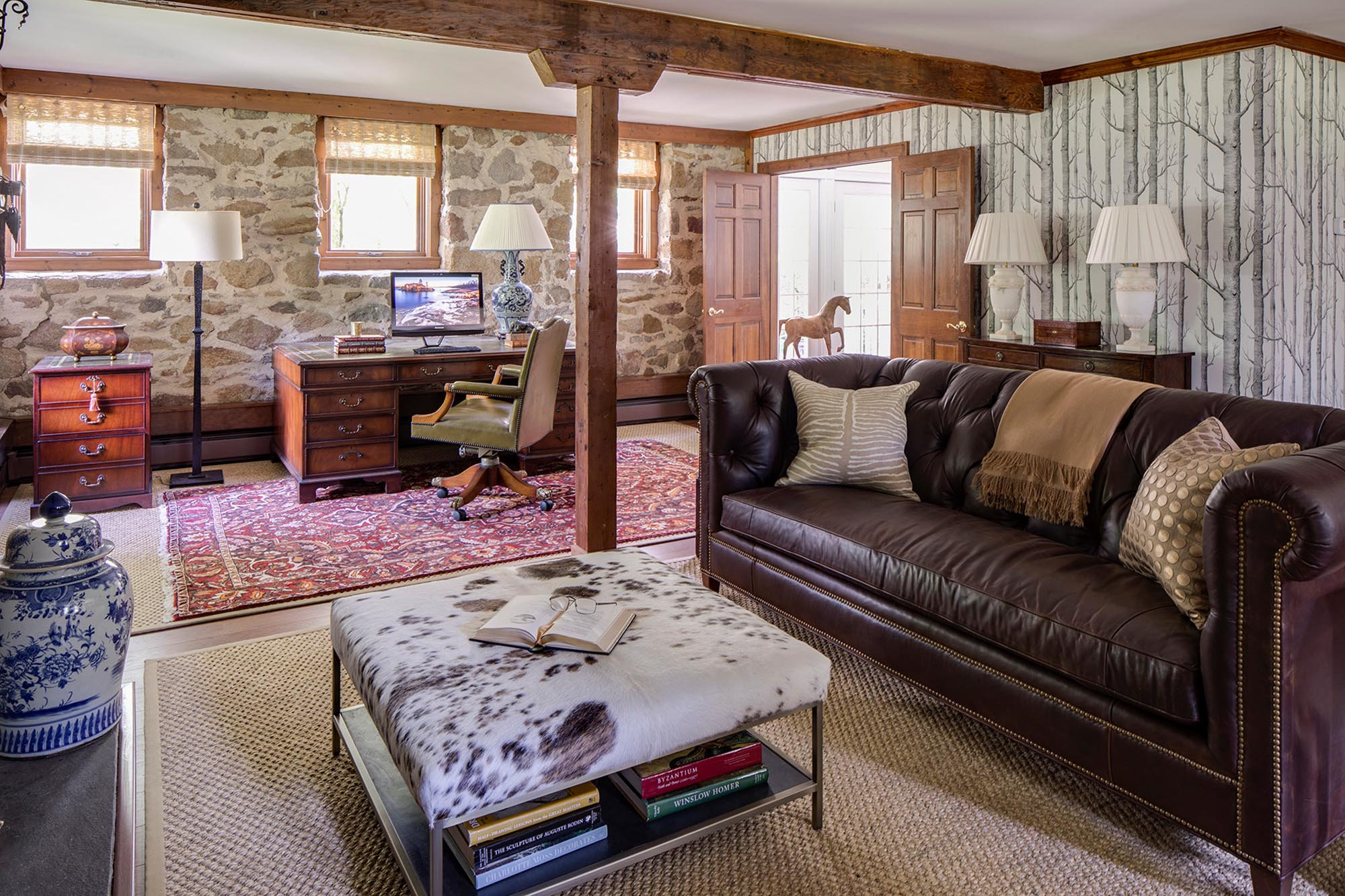 Living room with leather sofa and stone wall