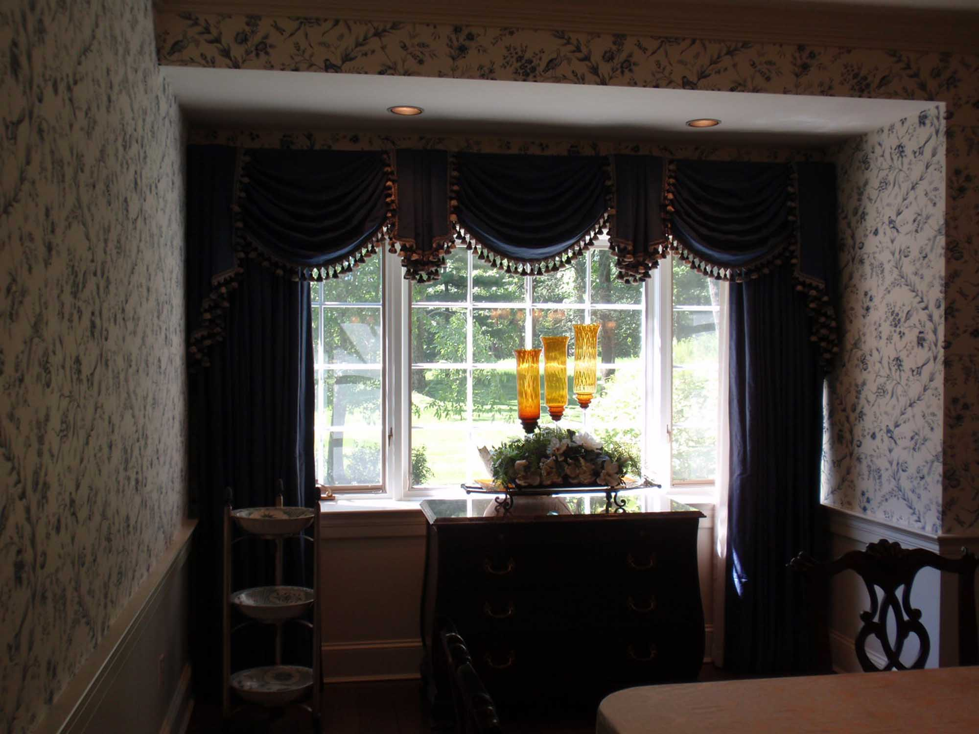 Dining area in printed wallpaper and blue curtains