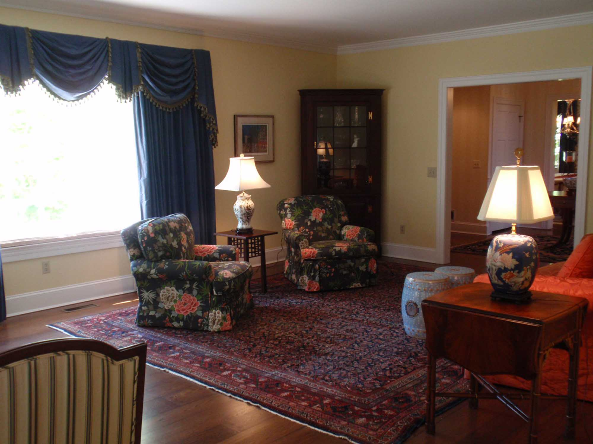 Living room with blue curtains and two couches in flower prints