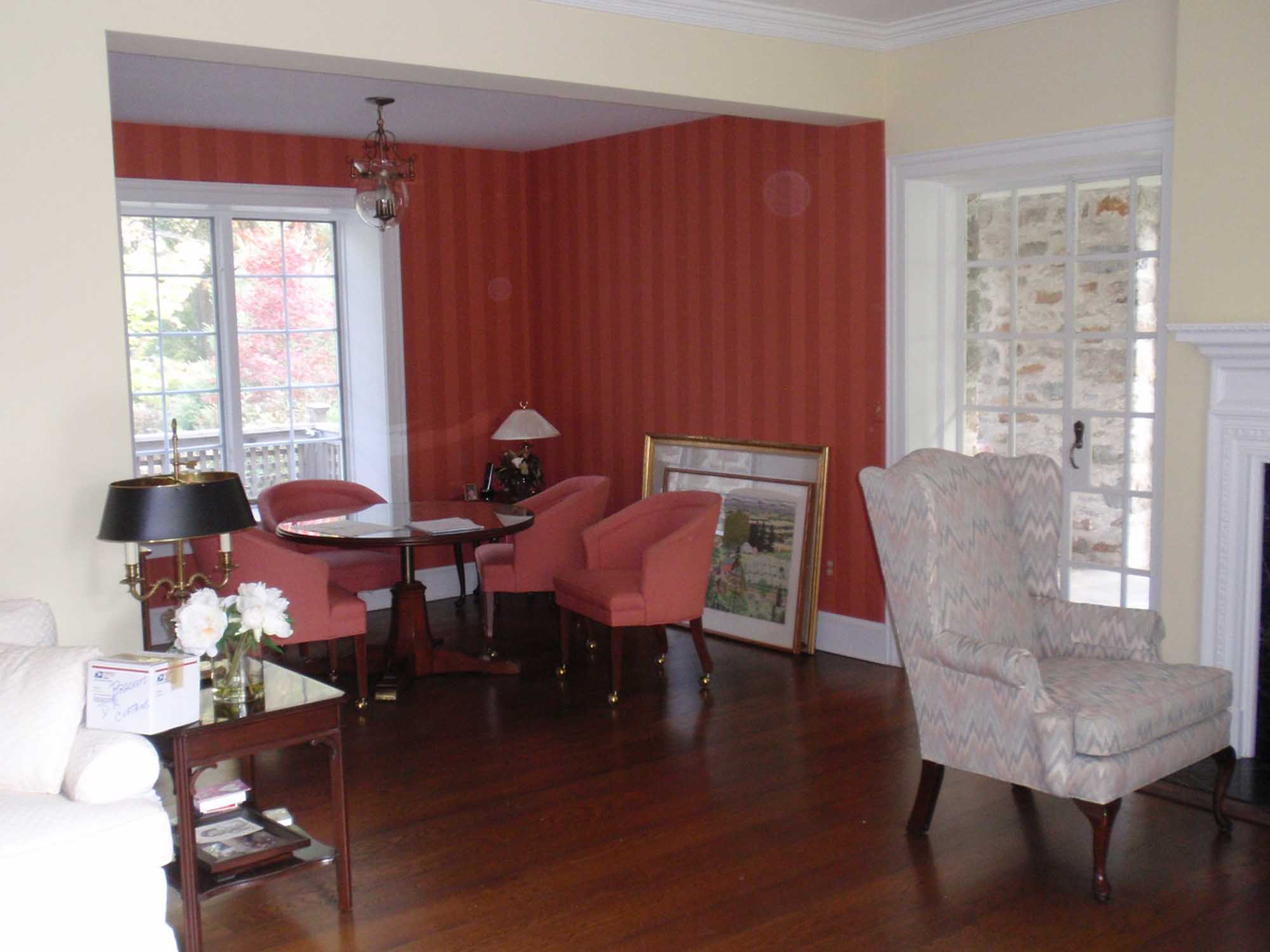 Dining area with red wallpaper and glass table for four