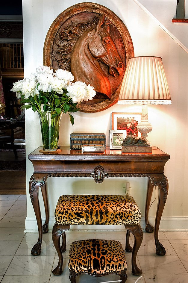 Wooden side table with wooden horse sculpture and flowers