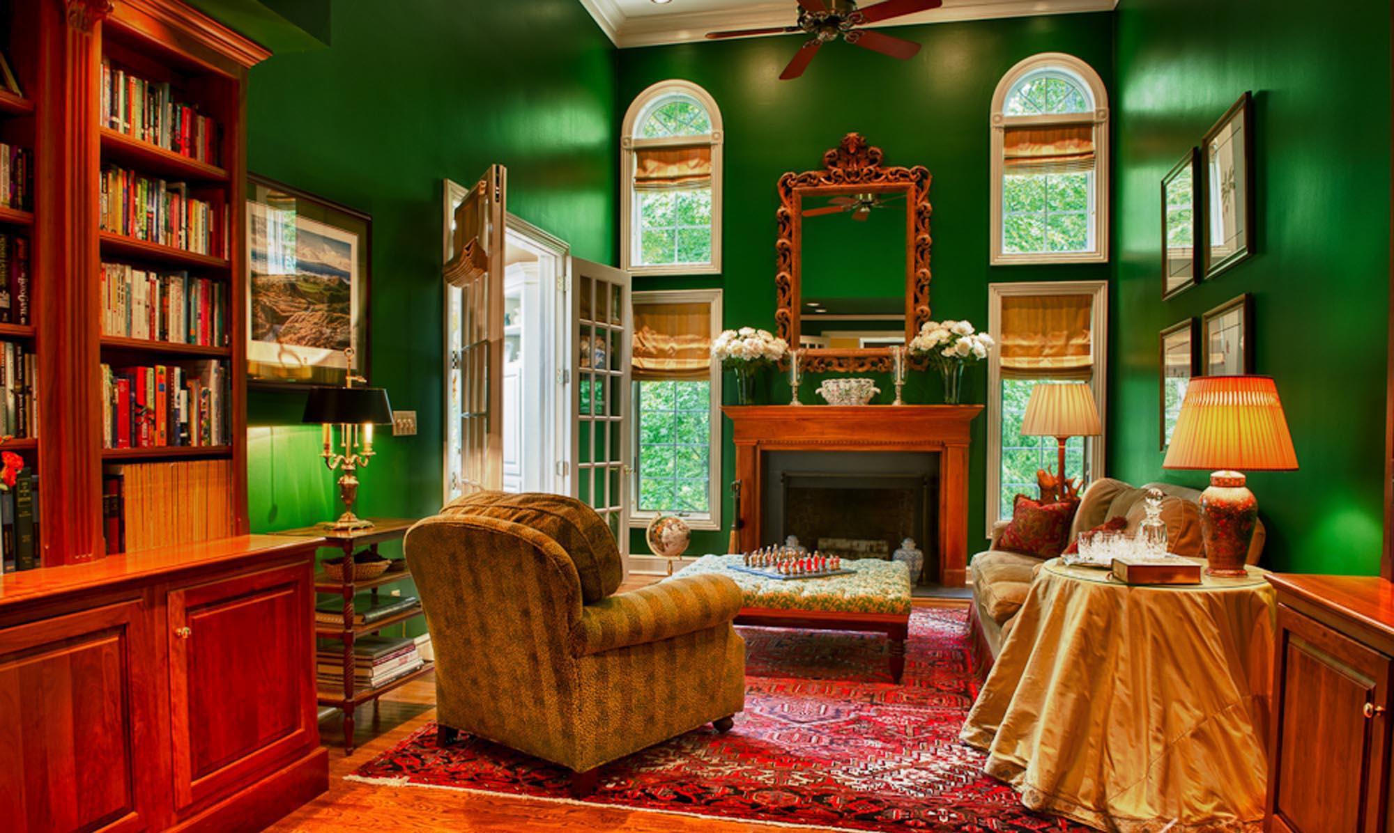 Warm living room in green paint with printed carpet and fireplace