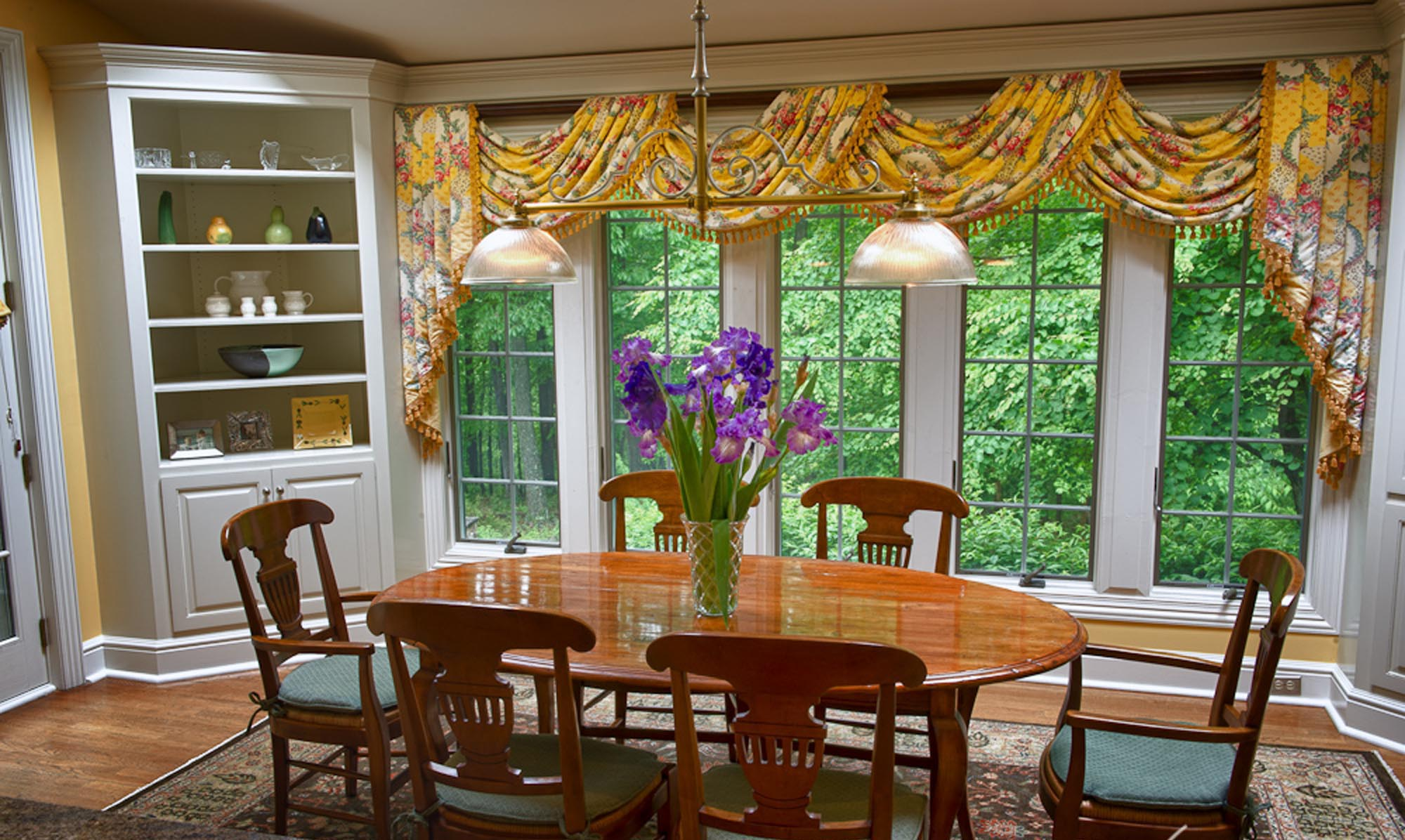 Bright dining area with wooden table for six and flowers