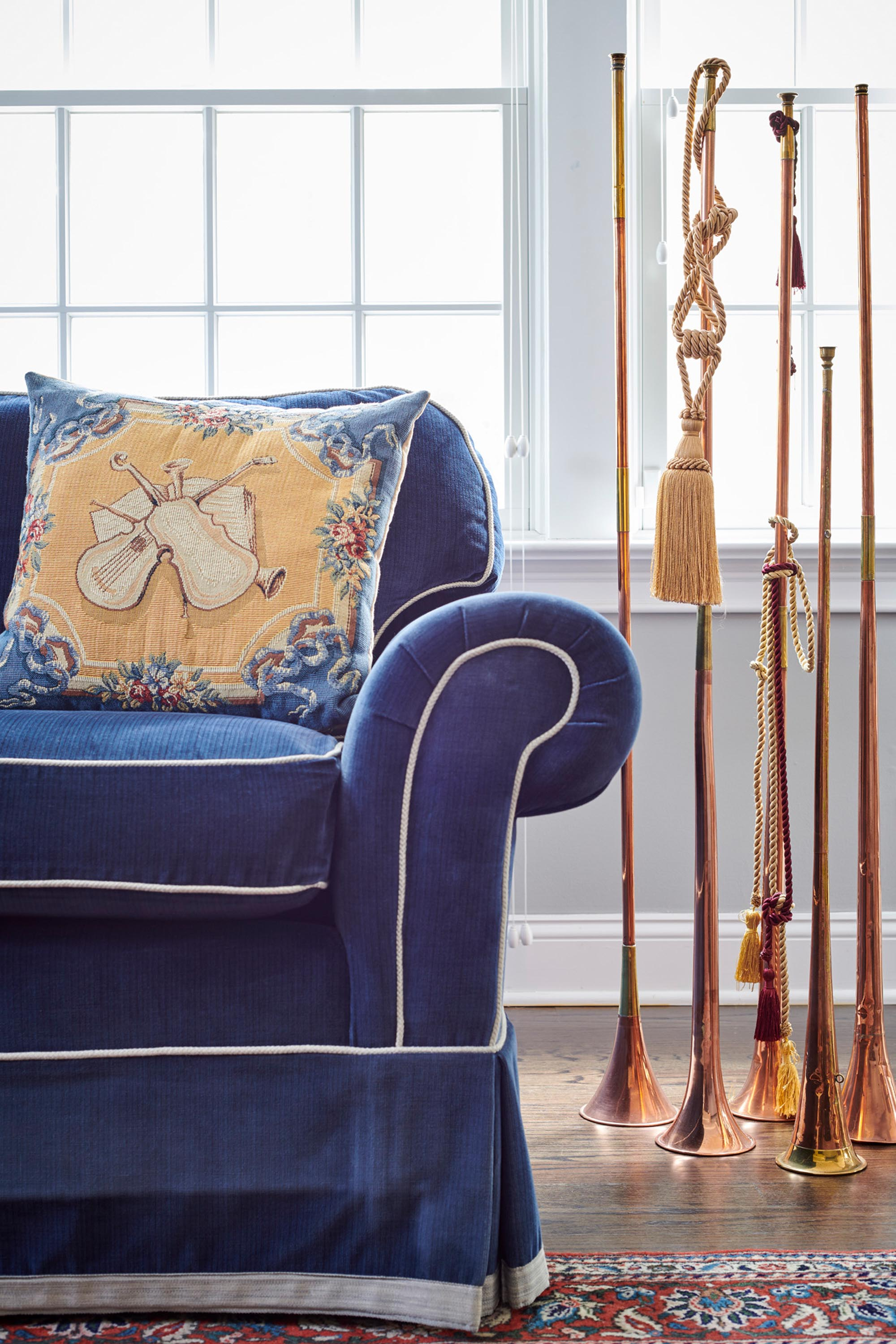 Custom blue sofa with tall brass decorative standing horns