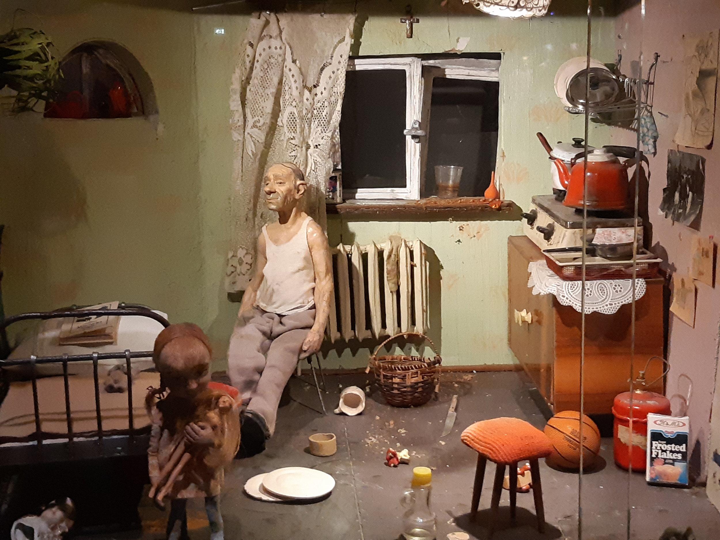 Alakerran asukas on sotkuinen ja ylipainoinen, yksinäinen mies, jota ympäröivät kaikenlaiset kulutushyödykkeet elektoroniikasta elintarvikkeisiin.  Nukkien tekeminen oli tärkeä elinkeino Althamerin perheelle 1990-luvulla, ennen kuin hän vakiinnutti asemansa taiteilijana.