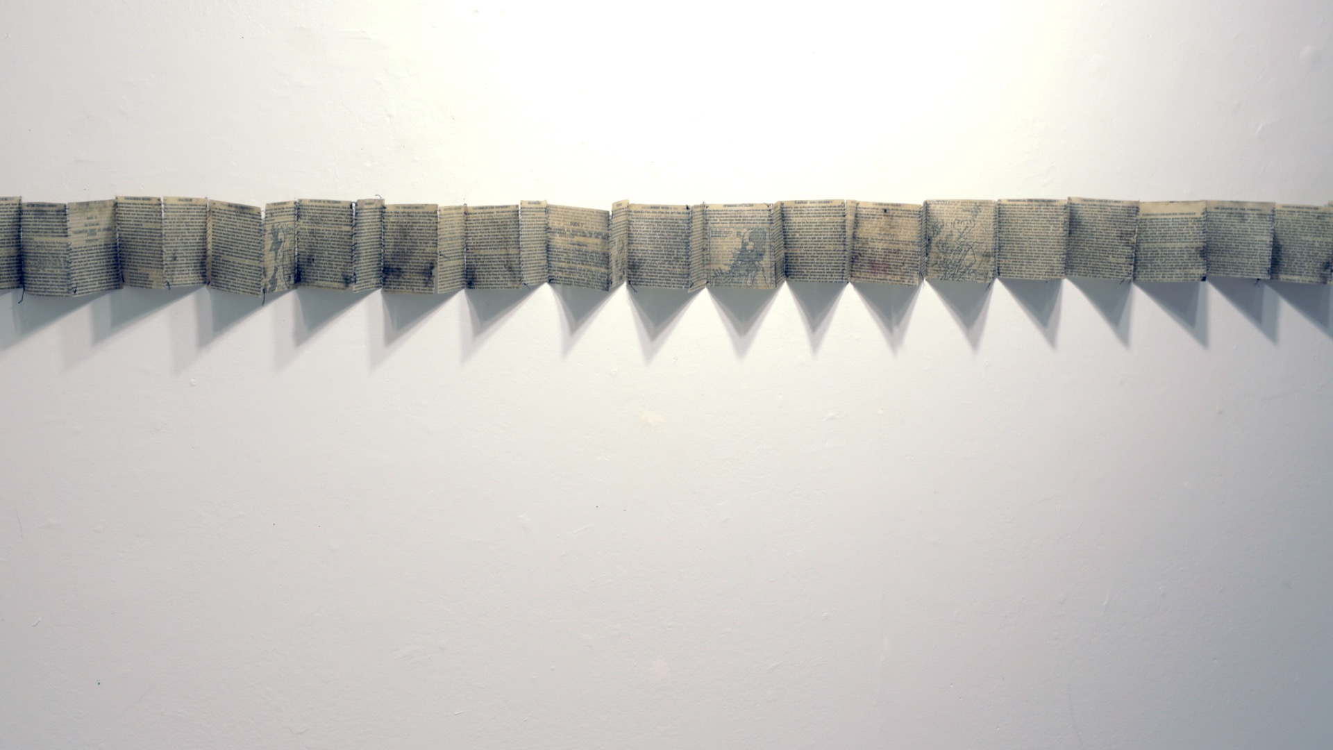 "History of England stitched and folded  / Book pages, beeswax, thread / 10 cm (4"") x variable (this installation 250 cm [9'] ) / 2018"