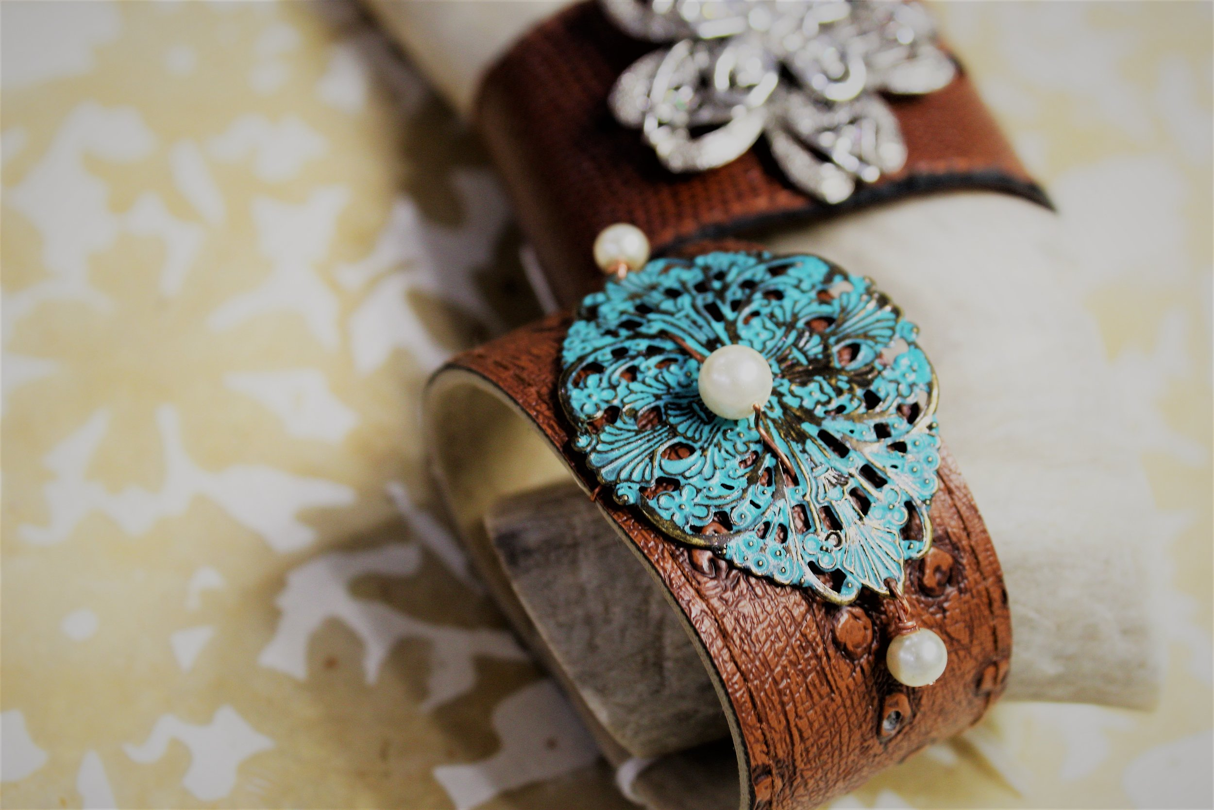 Leather cuffs by High Strung Jewelry, priced at $25. Jill Hernandez, jewelry designer uses a mix of genuine stones, Swarovski crystal and glass bead for majority of her pieces. We fell in love with these leather cuffs, and they worked perfectly to merchandise on our little deer antler and opaque floral papers. Stop in to see her other beautiful bracelets ($15) and earrings, (1 for $7 or 2 for $10) and her uniquely beaded necklaces ($22-$35).
