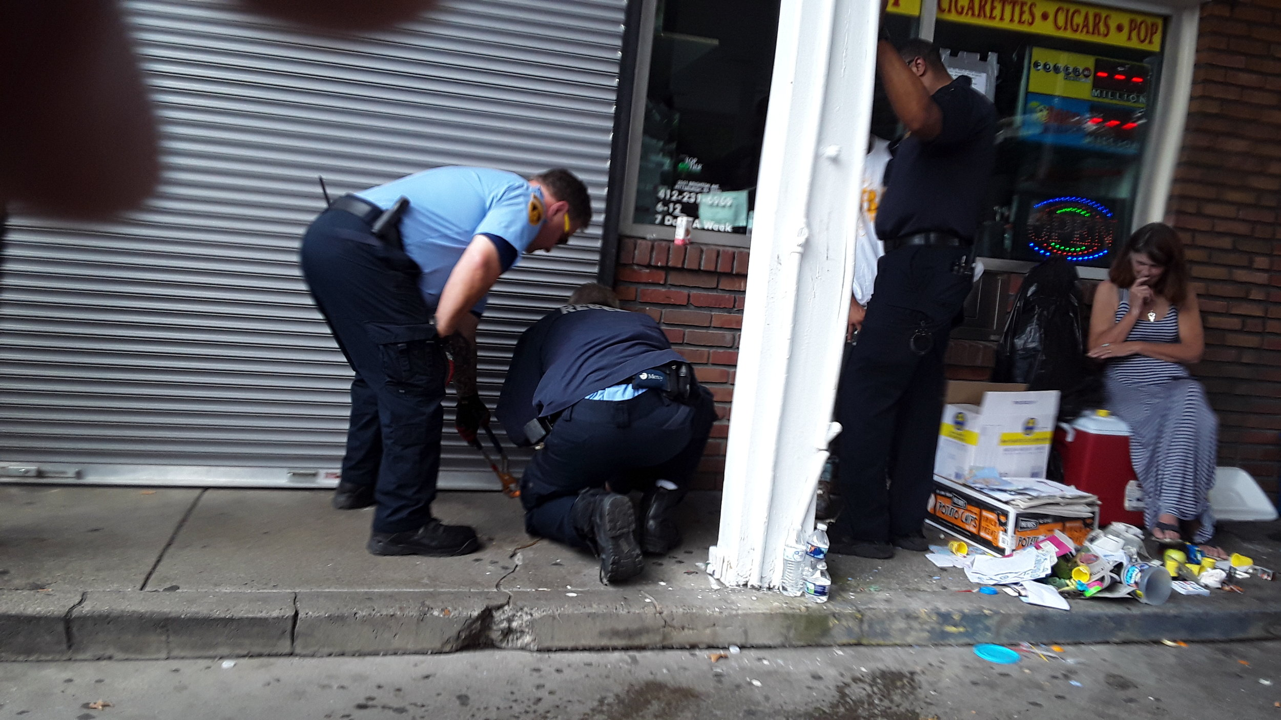 Three police officers examine the sidewalk in front of a gas station.