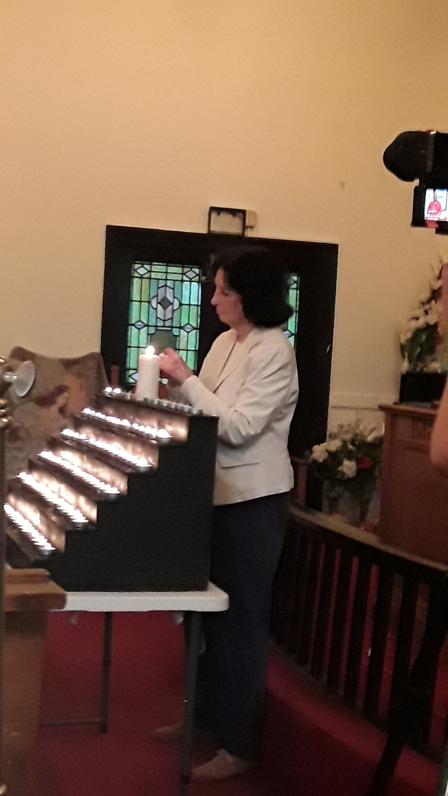 A woman lights a candle.