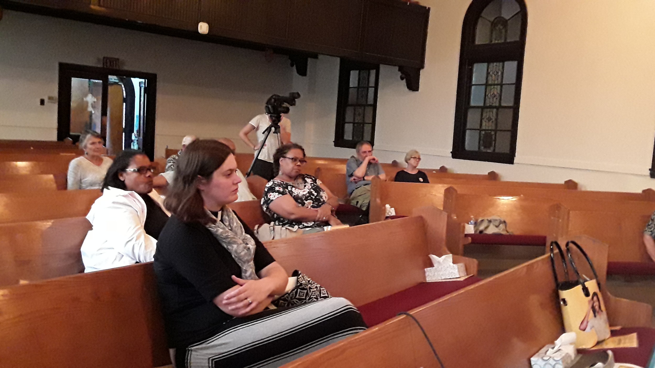 Attendees watch in pews.