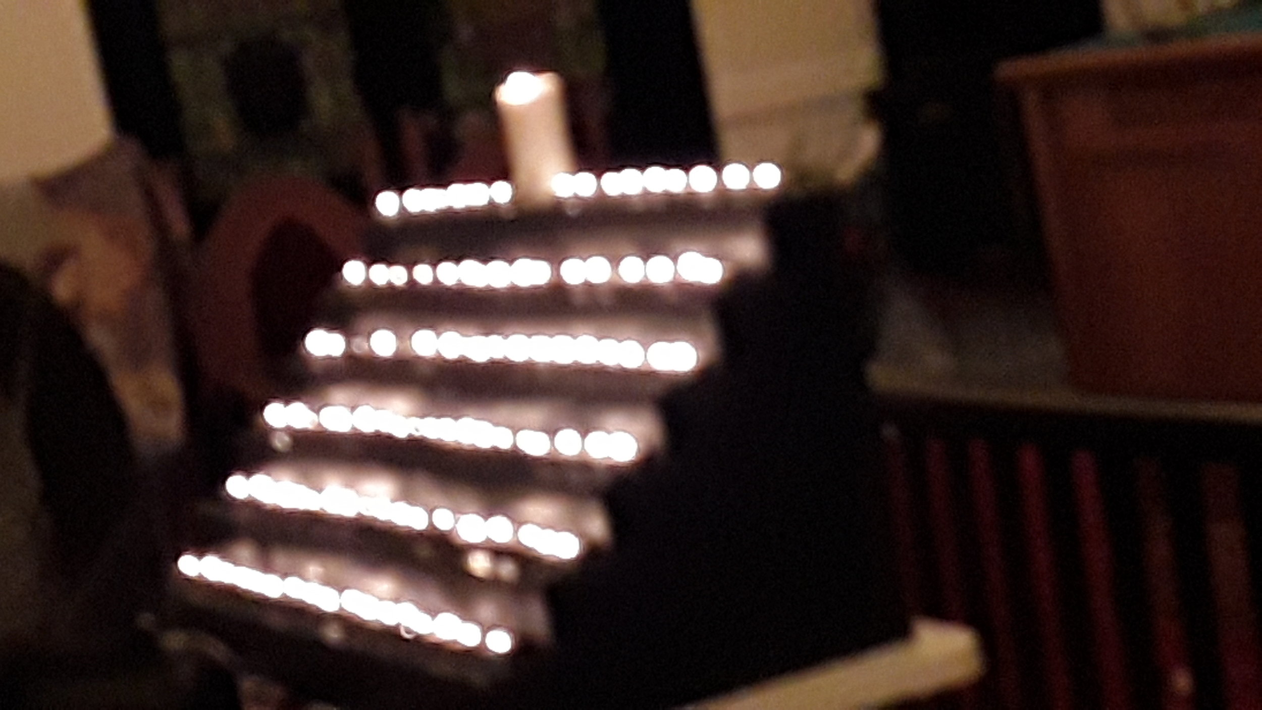 A display of several dozen lit candles.