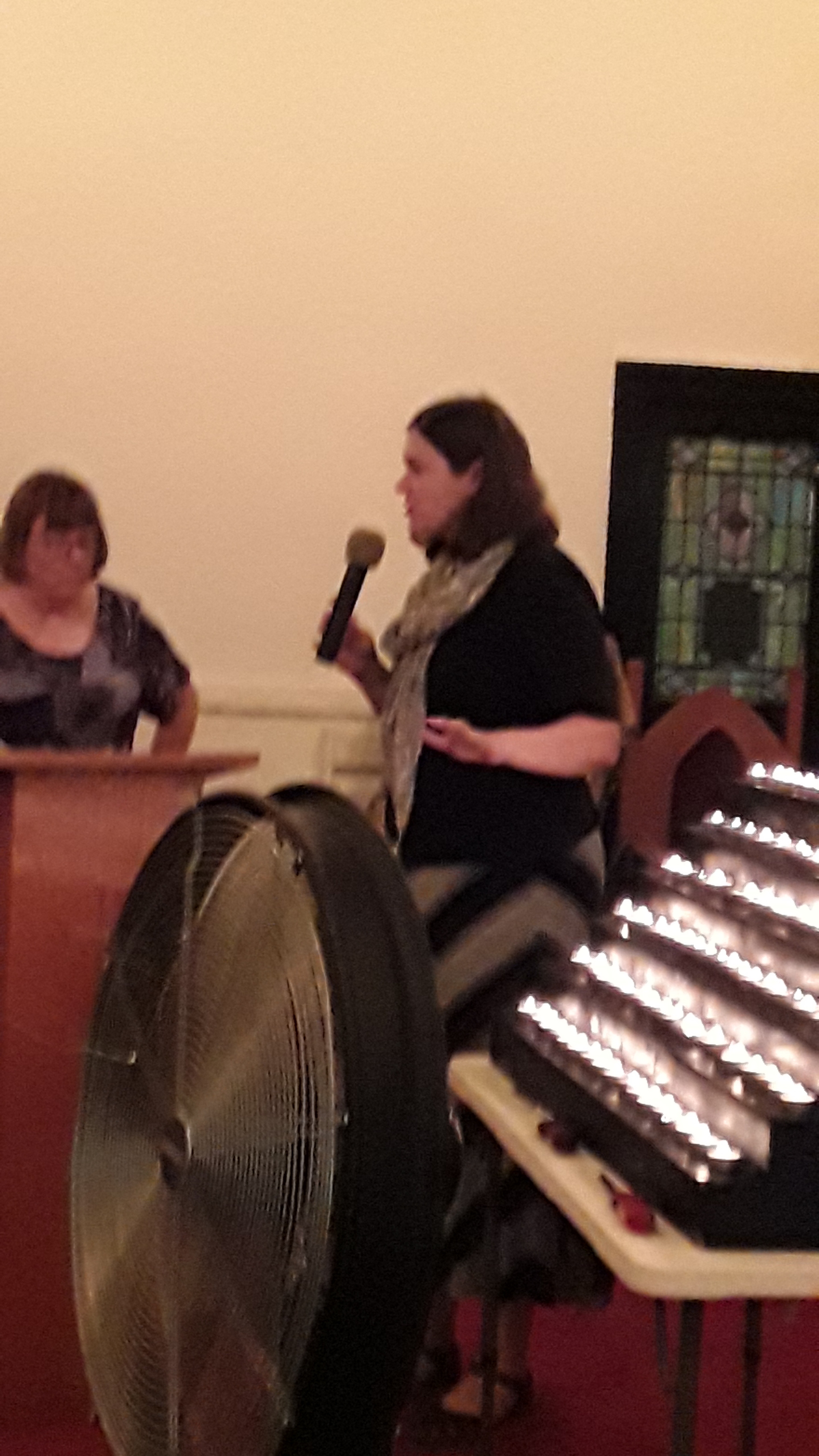 A white woman with a microphone speaks in front of a display of candles.