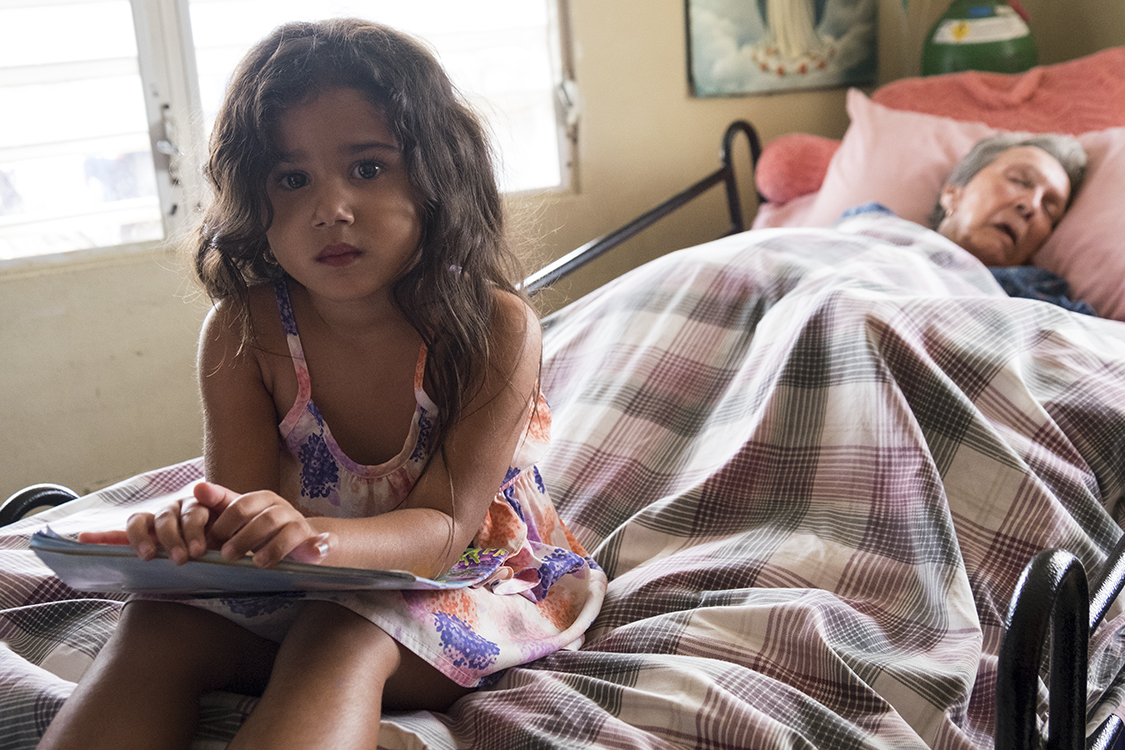 A young girl sits at the edge of her sick grandmother's bed. Family is very important in Puerto Rico, with many generations often living together or very close.