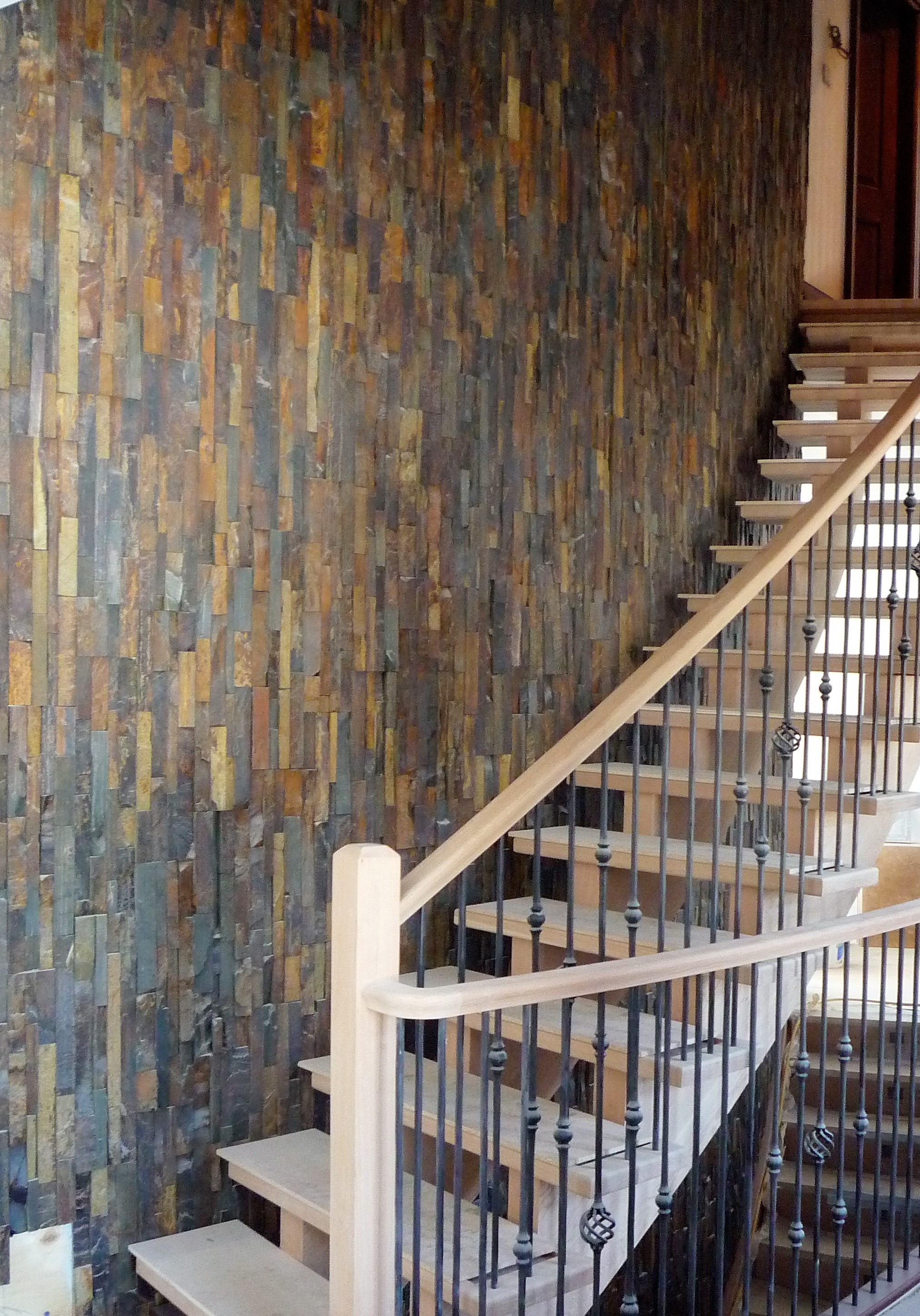 Living area hardwood staircase stone wall.jpg