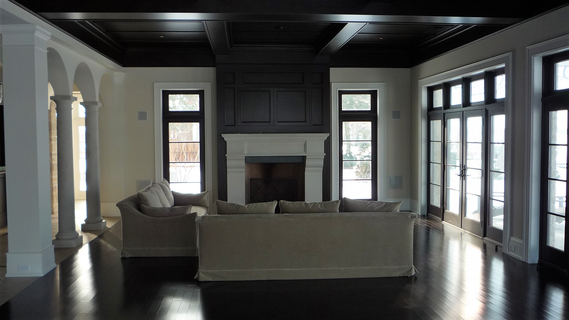 Living area walnet hardwood floor fireplace white mantle.JPG