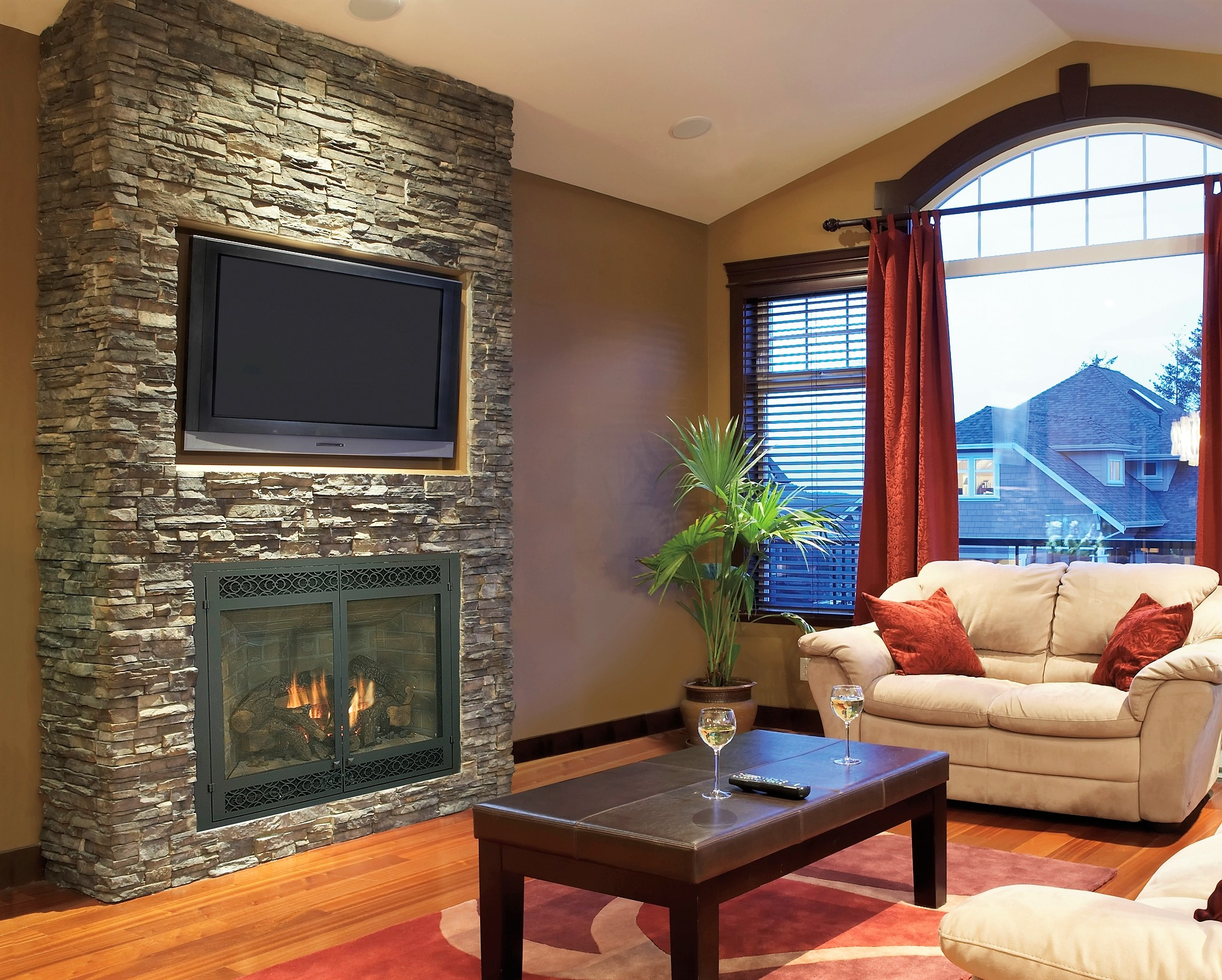 Living area stone fireplace surround hardwood floors carpet area rug.JPG
