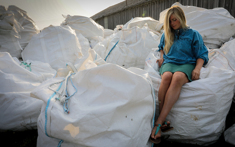 "Lilly Woodbury sits atop a stack of ""Supersacks"" – bags for transporting collected beach debris from remote sites to Tofino and then the mainland. Tofino, BC."