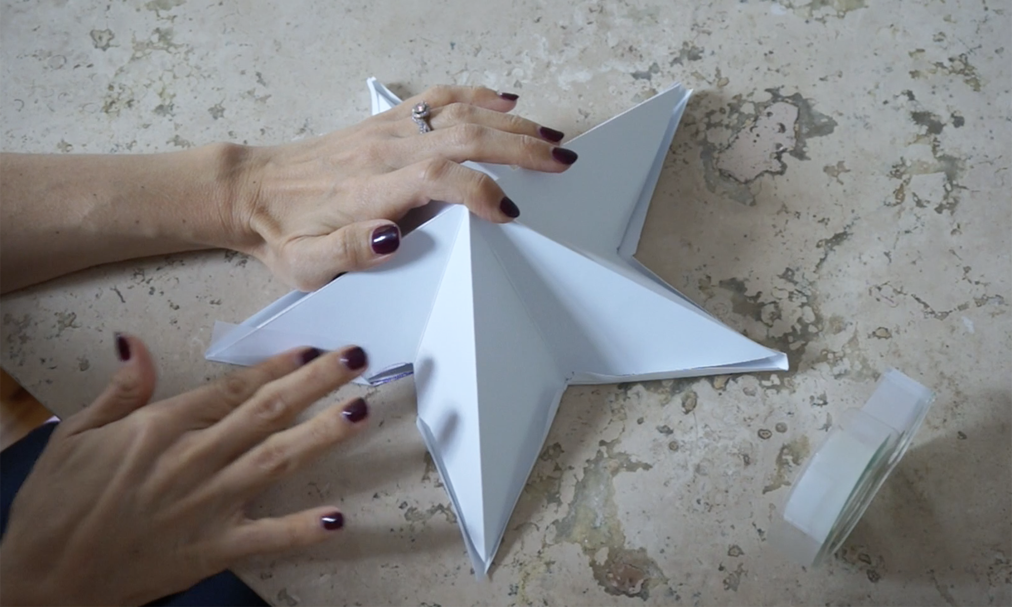 fold the edges over and tape the two pieces together /  pega las hojas de cartulina con cinta