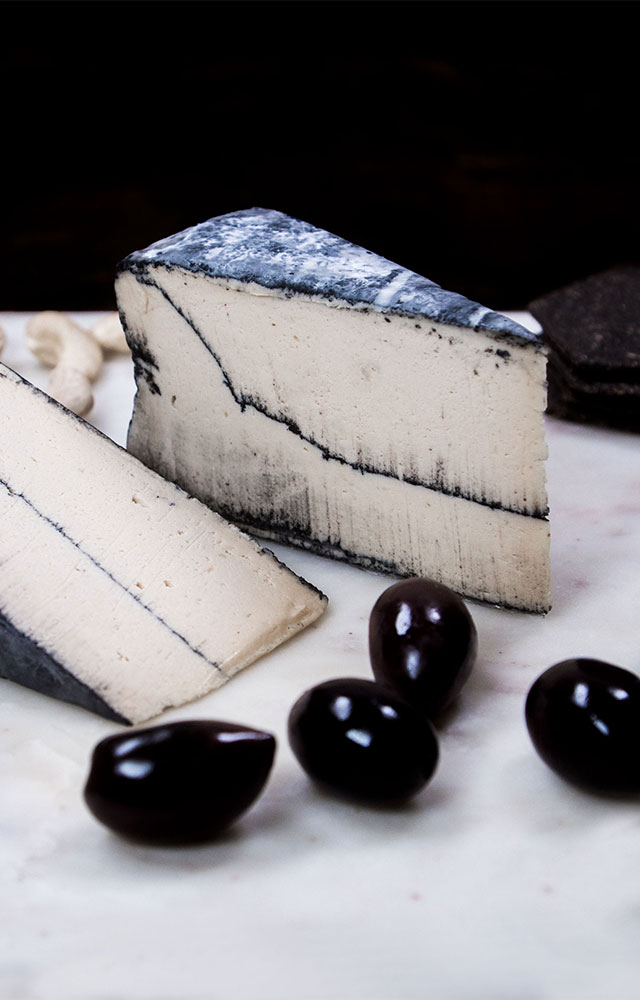 MINERTHREAT - Our signature cheese - a bold, smoky cashew cheese ripened in a coat of activated coconut charcoal.