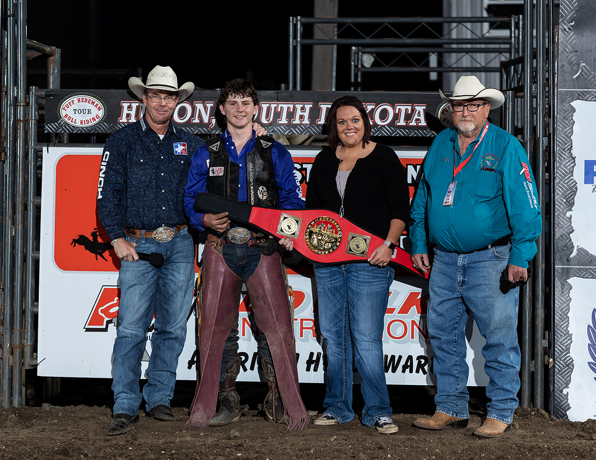 Jenny and Red Wilk present Trey Holston with the custom trophy belt for winning the Red Wilk Construction Bull Bash Breakout Series event on night one of the 2018 South Dakota State Fair.