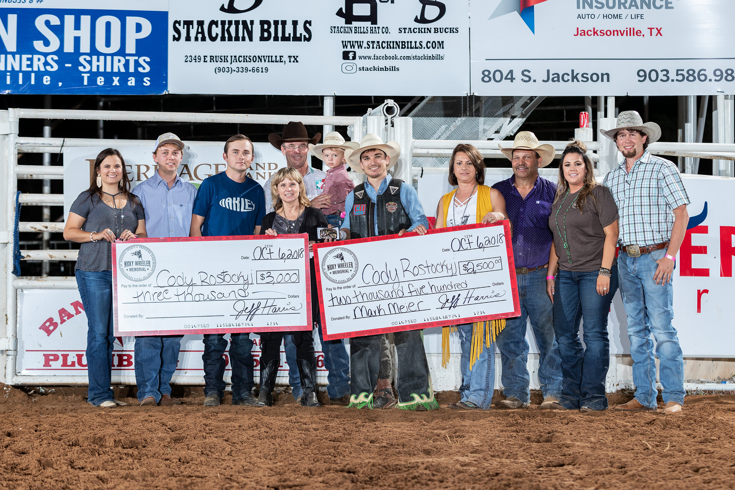Tuff Hedeman presents the check to last years champ Cody Rostockyj. The Nicky Wheeler Memorial Bull Riding serves as the primary fundraiser for the youth of Cherokee County. Co-Producers, Jeff Harris and Family, Haley and Brian Beasley with the Nicky Wheeler family, and Tuff Hedeman and son. Photo by Todd Brewer.