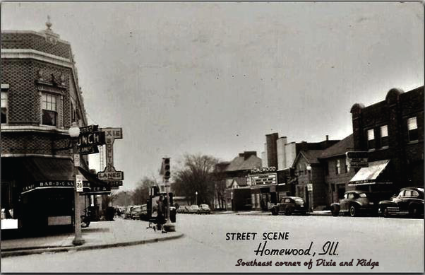 This is a photograph of a street scene in Homewood back in the late 1920s. The building on the corner to the left is now Copper Still Martini Bar & Lounge and 'Under the Still' is BLIND TIGER.