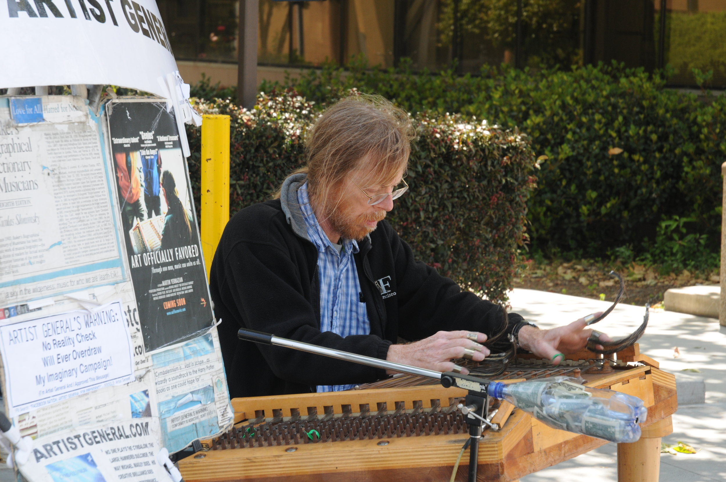 """Michael Masley, aka """"The Artist General"""" - Slide-Hammer AutoharpSATURDAY: 2454 Telegraph at Haste, - 2 pm on &SUNDAY: on Channing Ave, next to The Bird, 2400 Telegraph - 2 pm onIf you follow celestial sounds of music wafting through the air, you'll likely find local street musician treasure, Michael Masley. He is a unique American composer, instrumentalist, & inventor of musical instruments. You can hear & see his sonic inventions on youtube """"COLLATERAL TIMBRE Tools of Engagement"""".This """"Beethoven"""" of the streets, creates sounds that are full of harmonic resonances & tones expanding & rippling over each other. This music is soothing and creates wonder. It is defined by unusually complex textures.The most famous instrument in his menagerie of musical inventions is the """"bowhammer cymbalom"""". The Slide-Hammer Autoharp is his new muse. It is derived from the autoharp, where one depresses a button which dampens all the strings except for chords which the player strums. Michael multiplies sounds & rhythms by sliding a metal bar over the strings which stretches tones, and by plucking strings. More at: https://www.artistgeneral.com/"""
