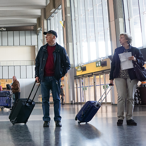 Older couple carrying luggage looking in the same direction