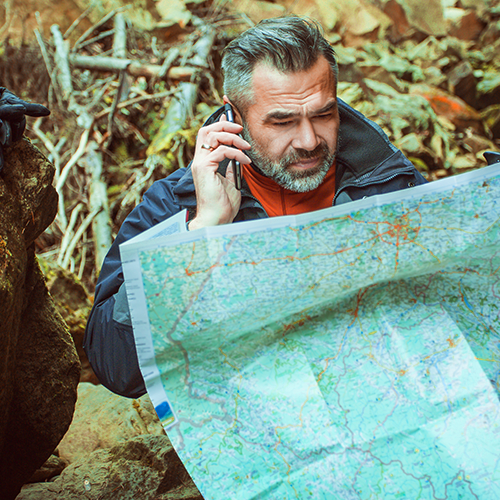 Adventurer squinting at a map and having a phone call