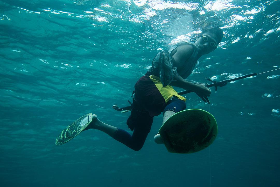 手作りのフィンとゴーグルで潜る現地の人